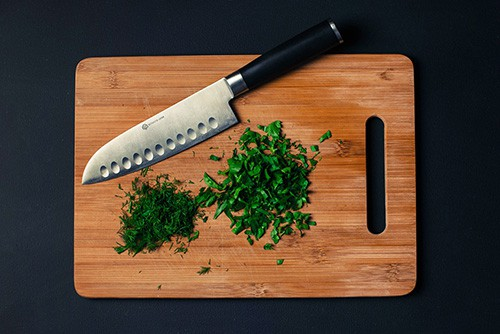 Cutting board with knife and chopped parsley