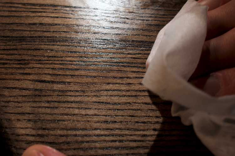 Male hand applying wood care products on a wooden bord with white cloth. Stock footage. Close up of wooden panel oiling process.