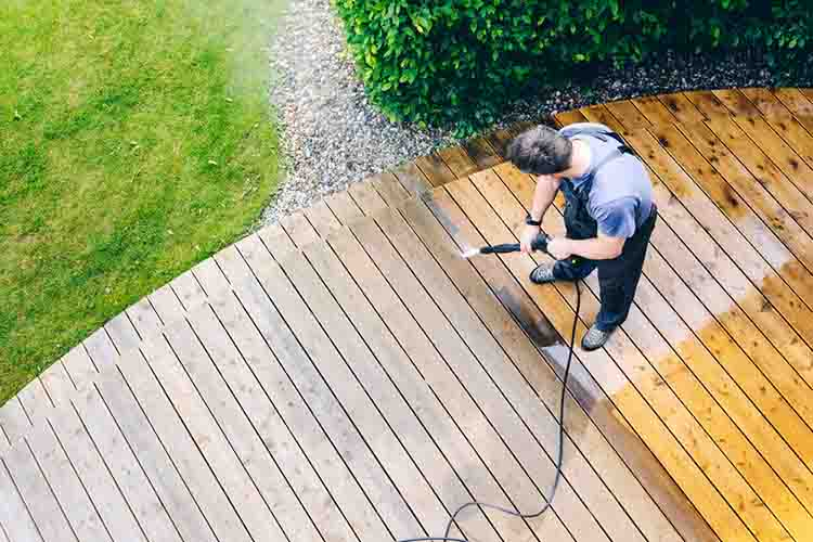 man cleaning terrace with a pressure washer