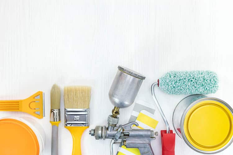 various painting tools on white wooden background
