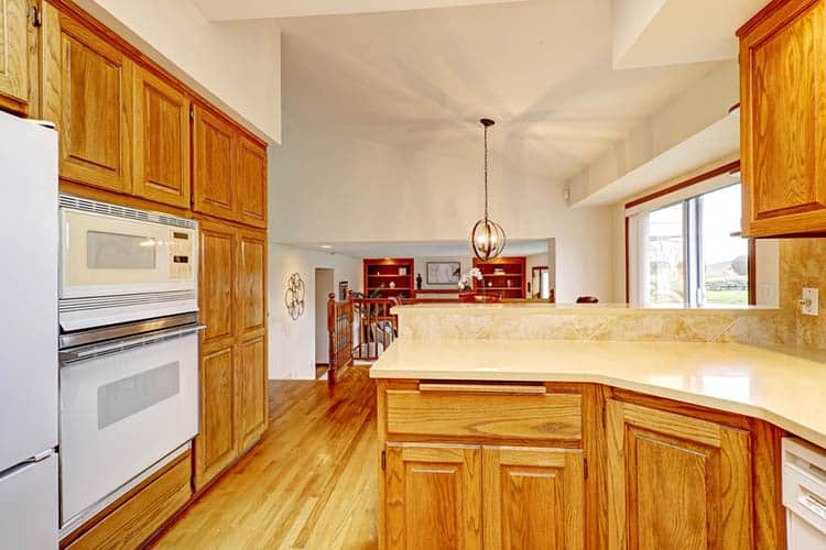 Open large kitchen interiorr with vaulted ceiling and white appli