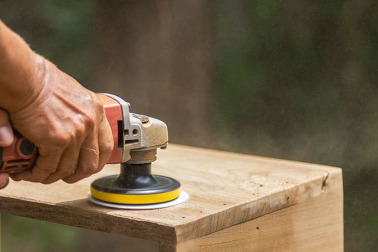 The carpenter uses a polishing machine to smooth the wood.