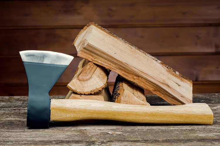 Axe and firewood, against the background of wooden boards.