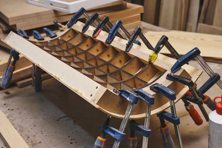 Joinery. Plywood bending process. Gluing and clamping bend wooden panel. Bend furniture manufacture