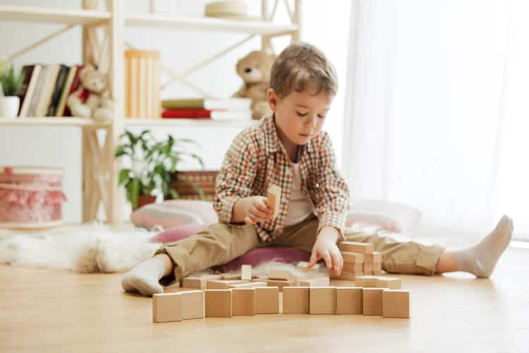 Little child sitting on the floor. Pretty boy palying with wooden cubes at home