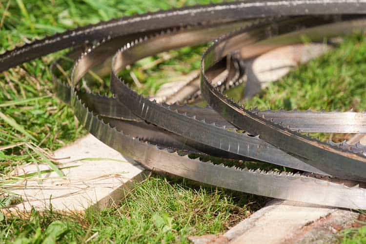 band-saw blades stacked on the ground