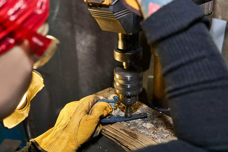 female artisan works on a drilling machine with a countersink close-up