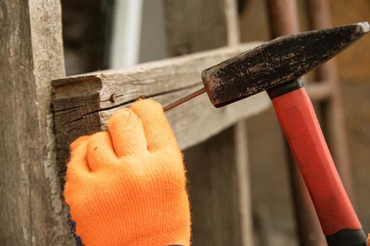 Hand in orange gloves hammer a nail