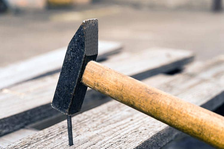 Close-up hammer that drives a nail into the board