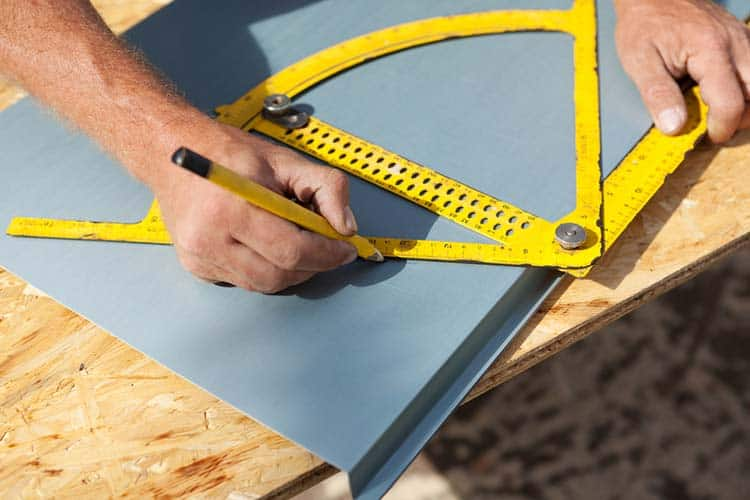 Roofer working with a protractor on a metal sheet