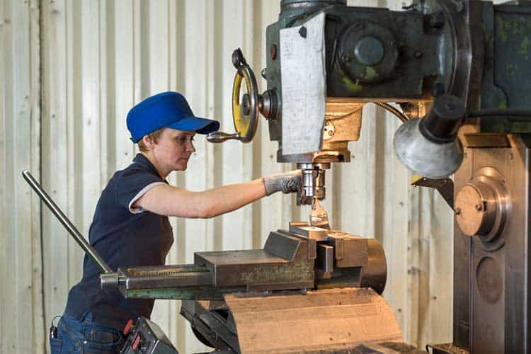 A woman at work on a vertical milling machine. Machining of a metal part on a metal-cutting machine.