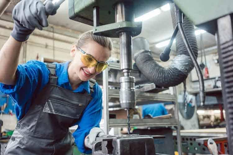 Woman worker in metal workshop using pedestal drill