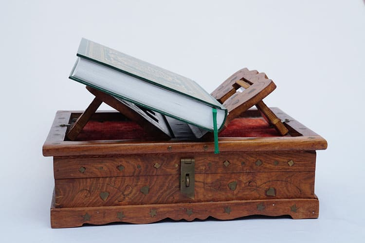 Muslim Coran on wooden book stand on white background