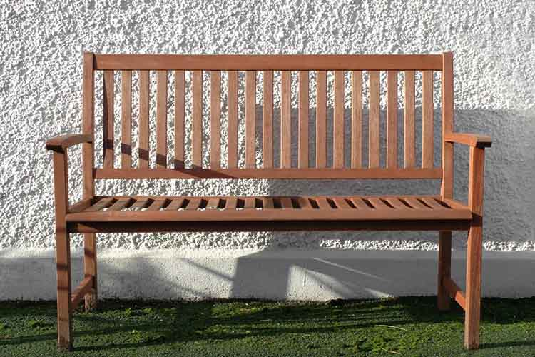 wooden bench against a white stone wall