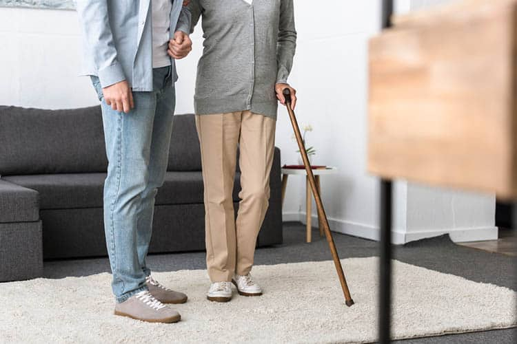 Cropped view of man helping senior mother with cane at home
