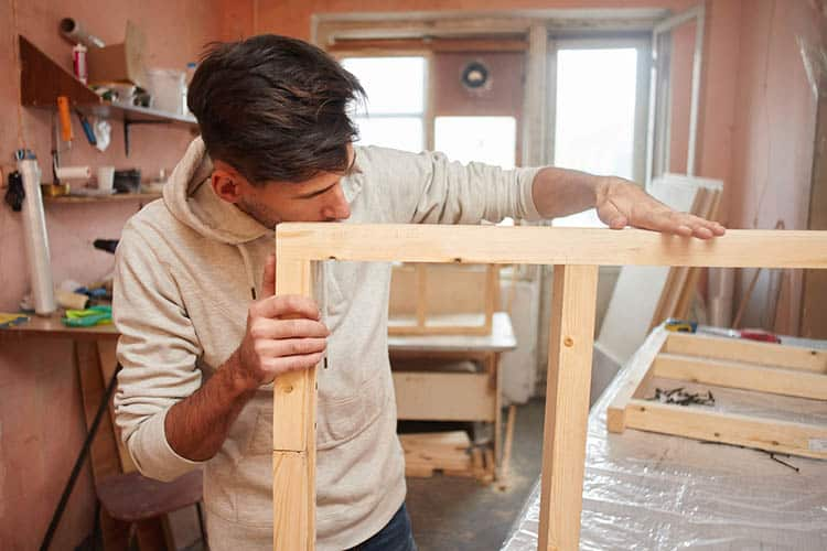 Portrait of a guy working in a home workshop