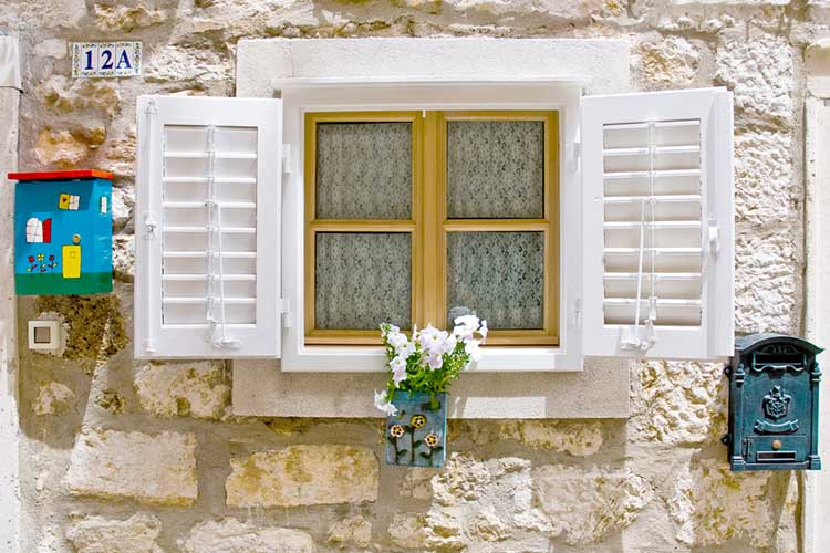 Old styled European window with shutters, flower box and mail box